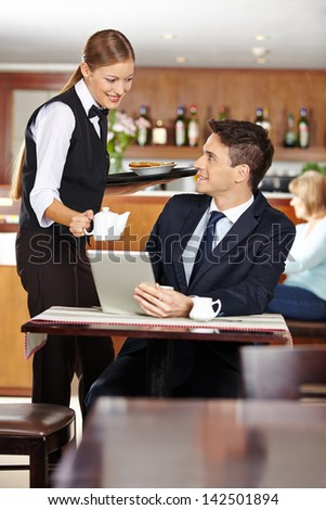 Female waiter serving businessman in coffee shop a pot of coffee - stock photo