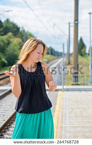 Female waiting train on the platform of railway station - stock photo
