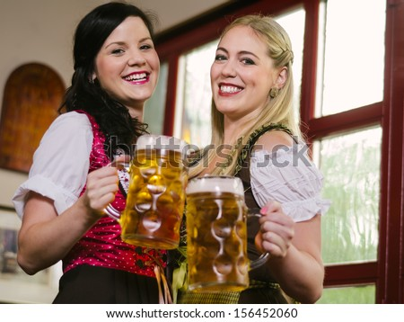 female waitresses wearing traditional dirndl and holding huge beers in a pub. - stock photo