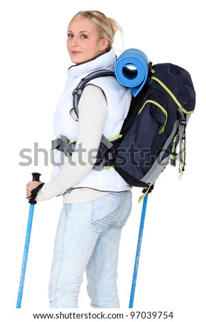 Female walker with poles and a backpack - stock photo