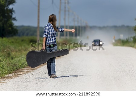 Female walking down a dirt road hitchhiking with a guitar case - stock photo