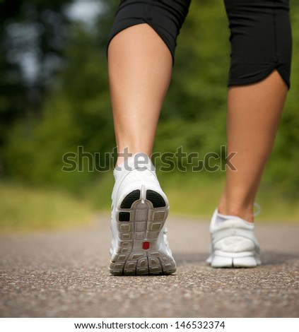 Female walking on path in running shoes from behind - stock photo