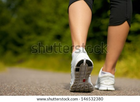 Female walking outdoors in running shoes from behind - stock photo