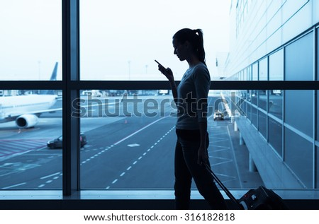 Female walking through the airport using her smartphone device.  - stock photo
