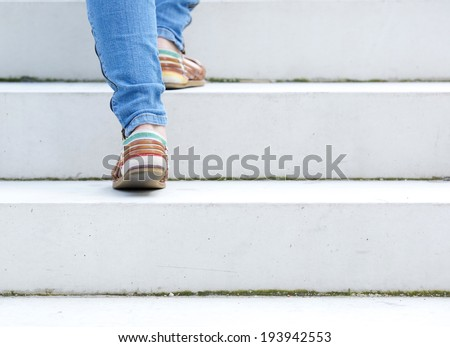 Female walking upstairs on stone staircase outdoors