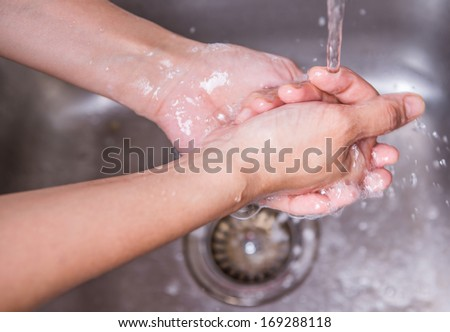 Female washing hands at the kitchen sink - stock photo