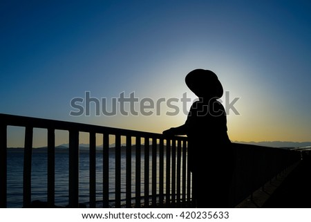 Female Wearing Sun Hat Standing By Railing Taking In The Sunset Silhouette