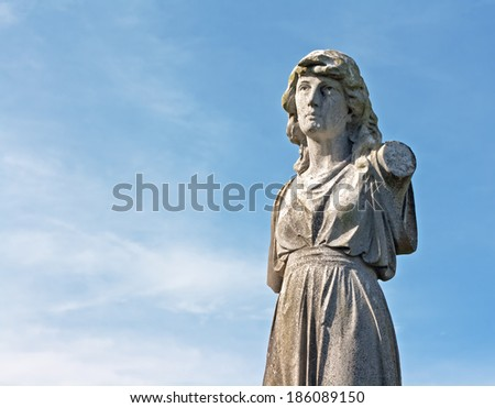 Female weathered statue in ancient graveyard - stock photo