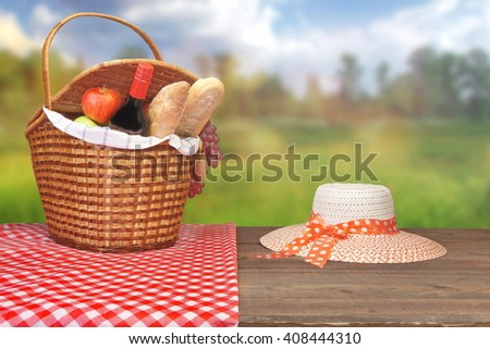 Female White Hat And Picnic Wicker Basket Close Up With Red Wine Bottle, French  Baguettes, Fruits  On The Wood Table And Rural Summer Landscape On The Blurred Background - stock photo