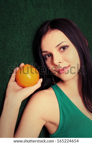 female with an orange in her hands, very closeup view, vertical shot - stock photo