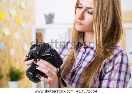Female with camera in hands on office background