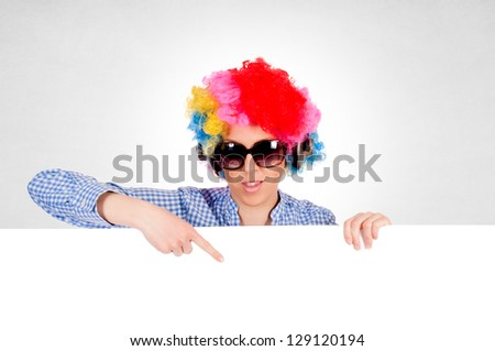 Female with clown wig pointing on the blank white space - stock photo