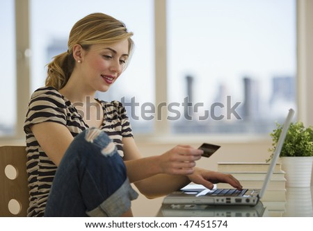 female with credit card shopping on-line from home