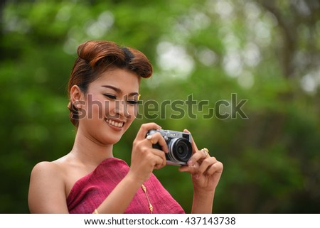 Female with dress thai costume holding a camera vintage