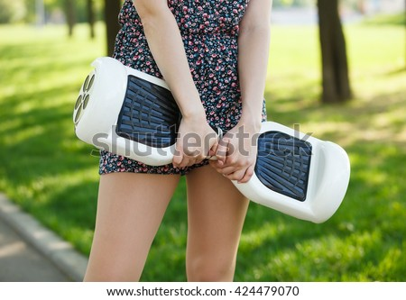 Female with electric mini hover board scooter in green park. Eco city transportation on battery power, produce no air pollution to atmosphere - stock photo
