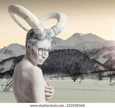 Female with goat body-art over winter countryside background. Dedicated to Chinese Horoscope 2015 - Year of the Goat (Sheep) - stock photo