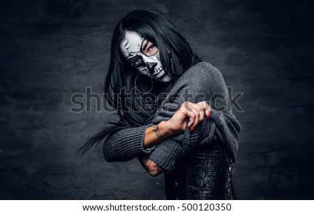 Female with skull make up undressing on dark background.