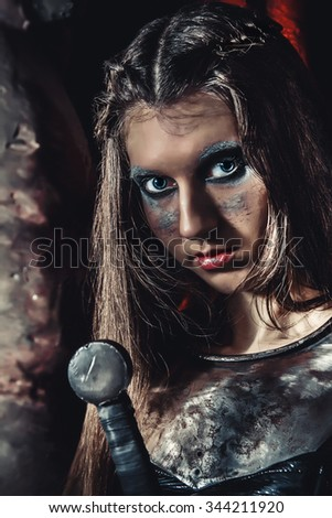 female with sword in a knight's armor on dark background - stock photo