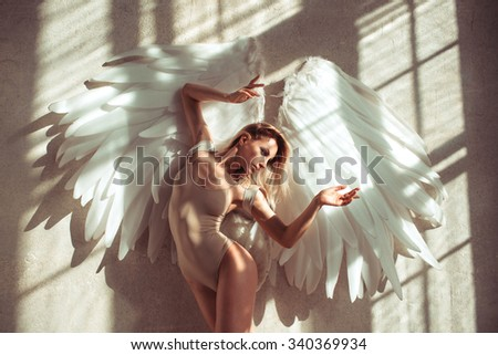 female with wings posing in studio - stock photo