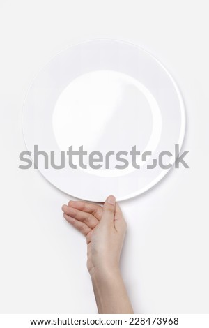 Female(woman) hand hold a white dish(plate) isolated white and top view. - stock photo