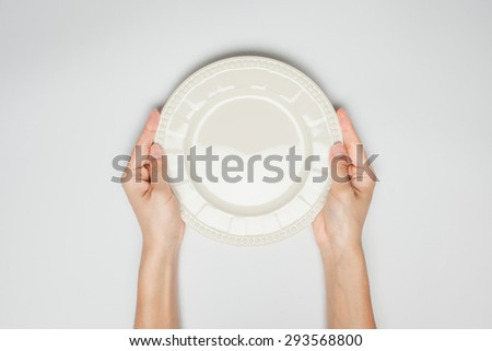 Female(woman) two hands hold(support) a dish(plate) isolated white and top view. - stock photo