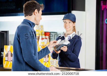 Female worker accepting payment from man through NFC technology at cinema concession stand - stock photo