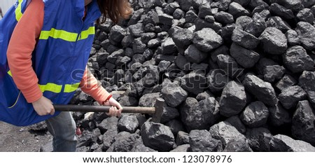 female worker breaking the coal using hammer