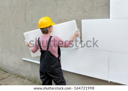 Female worker carry styrofoam sheet insulation at construction site - stock photo