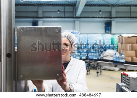 Female worker doing her job in water factory. Selective focus.