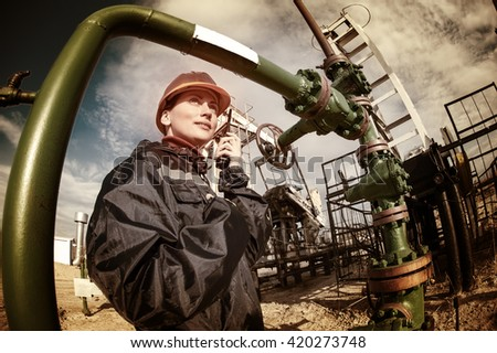 Female worker in the oil field talking on the radio wearing orange helmet and blue work clothes. Industrial site background. Toned. - stock photo
