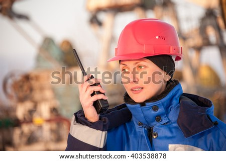 Female worker in the oil field talking on the radio wearing red helmet and blue work clothes. Industrial site background. - stock photo