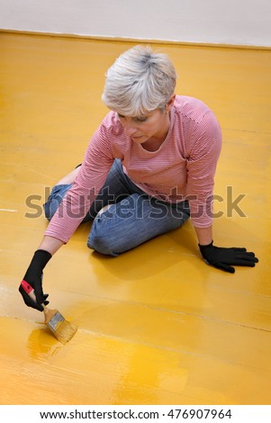Female worker painting wooden floor to yellow