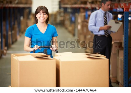 Female Worker Pulling Pallet In Warehouse - stock photo