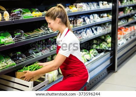 Female worker putting vegetable box in shelf in grocery store - stock photo