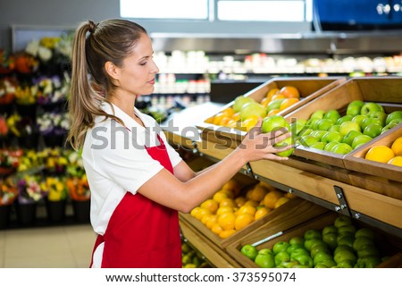 Female worker taking fruits in grocery store - stock photo