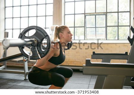 Female working out in a gym doing squats. Young woman working out using barbell with heavy weights in a fitness club. - stock photo