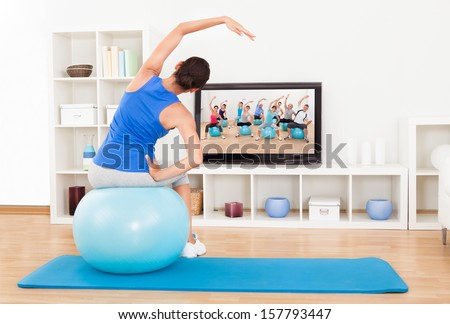 Female Working Out With An Blue Exercise Ball In Front Of Television