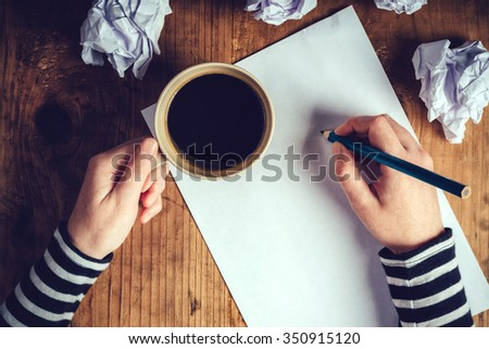 Female writer drinking cup of coffee, top view of female hands holding cup of coffee above pencils and paper on work desk, retro toned image.