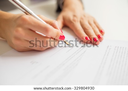 Female writing on paper  - stock photo