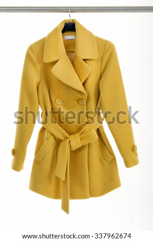 Female yellow coat clothing on hanging - stock photo