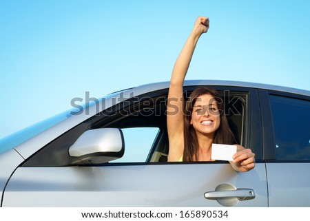 Female young driver in her car after passing the driving license test. Successful woman showing blank card in vehicle. - stock photo