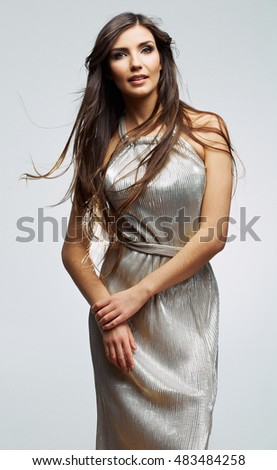 Female young model in silver evening long dress. Studio isolated beautiful woman portrait, gray background .
