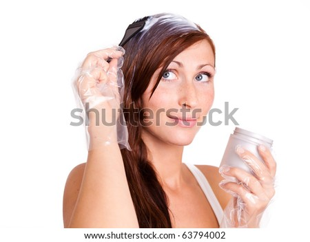 Female young woman coloring her hair applying color cream at hair isolated