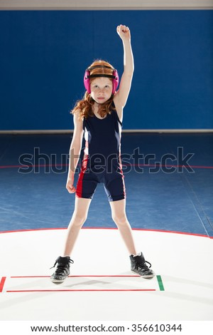 Female youth wrestler with her arm raised in victory - stock photo