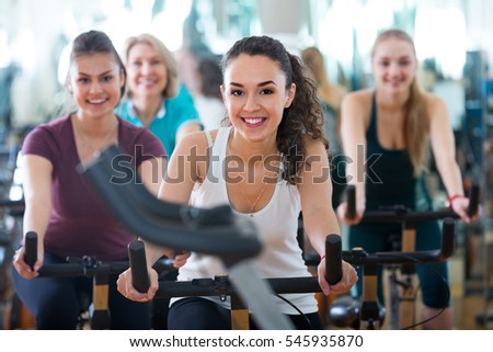 Females in track-suit riding stationary bicycles in modern gym for women