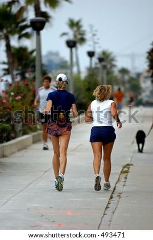 Females running along the beach. - stock photo