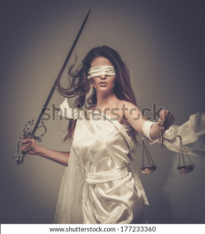 Femida, Goddess of Justice, with scales and sword wearing blindfold  - stock photo