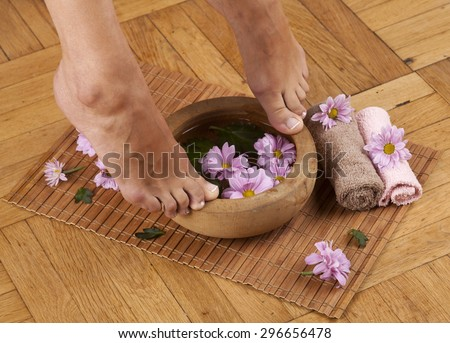 Feminine feet and foot spa bowl with flowers and towels