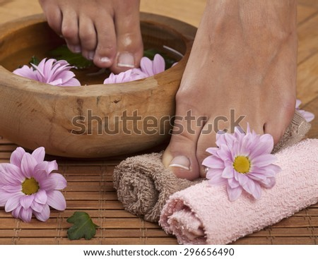 Feminine feet in foot spa bowl with flowers and towels - stock photo