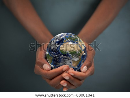 Feminine hands holding the Earth against a dark background - stock photo